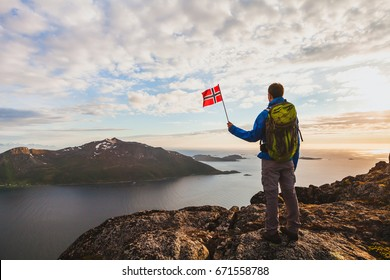 hiking in Norway, silhouette of hiker looking at beautiful fjord landscape and holding norwegian flag, adventure outdoors