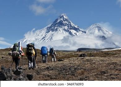 Hiking on Kamchatka Peninsula: travelers climbing to mountains on background volcanoes: Kamen Volcano, active Klyuchevskoy Volcano, Bezymianny Volcano on sunny day. Russian Far East, Kamchatka Region.