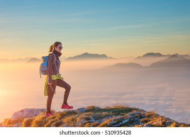 Hiking on mountain ridge in the sea of clouds. A girl alone