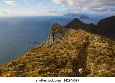 Hiking on top of scenic cliffs of island Vaeroy, Lofoten in Norway