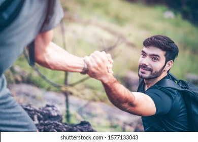 Hiking outdoor activity in summer, man helping to pull a beard guy climb on mountain. Climber teamwork trust and support each other to success. People holding hands to rescue team together.