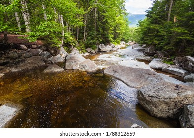 Hiking over the rivers that run down the White Mountains on the Pemi Trail in New Hampshire. Gorgeous landscape adventure background