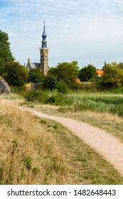 Hiking path along water in Veere, The Natherlands. With view on the Town Hall.
