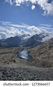 Hiking Path from Passo Presena to Passo Lagoscuro with Background of Mandron Glacier and Lake Lagoscuro and a cloudy blue sky