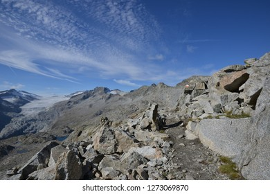Hiking Path from Passo Presena to Passo Lagoscuro with Background of Mandron Glacier and a cloudy blue sky