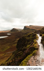 Hiking path at Quiraing on a moody cloudy autumn day with orange vegetation and panorama view of Skye (Isle of Skye, Scotland, Europe)