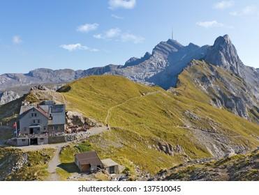hiking path through rocky mountainous ridges with rest house and leading up mountain Saentis, Switzerland