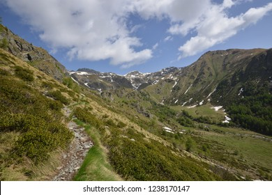 Hiking path in Val Bighera in Front of beautiful Mountains and a blue cloudy sky