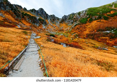A hiking path winding on the mountainside & the grass turning into orange color under rugged peaks of Komagatake Mountain in Senjojiki Cirque of Japanese Central Alps National Park, Nagano, Japan