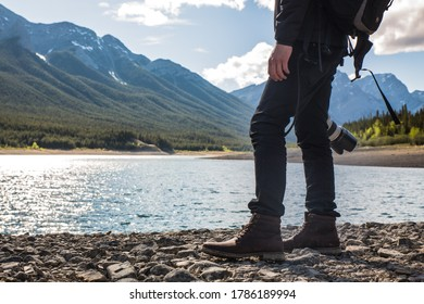 Hiking and photography attire and backpack to explore the mountains and lakes in Alberta. National park exploration and photography and hiking days. Outdoor walking attire on rocks by the lake.