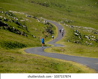 Hiking Pilgrims on a winding curved road on the El Camino de Santiago in Spain