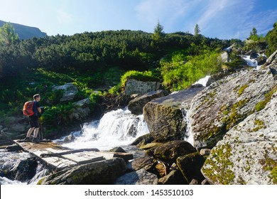 Hiking in Romania's Parâng mountains in summer - scene with hiker with backpack admiring a small waterfall while traversing a small mountain stream