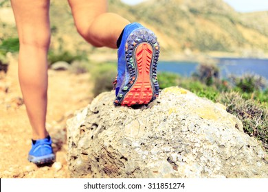 Hiking or running woman in beautiful mountains inspirational landscape. Sole of sports shoe and legs of person on rocky footpath. Hiker trekking or walking of footpath. Healthy lifestyle concept.