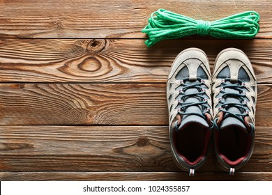 Hiking shoes and climbing rope over wooden background