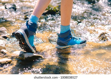 Hiking shoes - sole of trekking boots and legs in a mountain stream. Tourist trekking or walking sidewalk. Healthy outdoor fitness lifestyle
