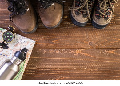 Hiking shoes with topo map and compass on a wood background.