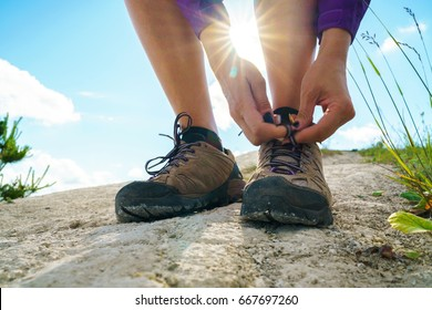 Hiking shoes - woman tying shoe laces. Closeup of female tourist getting ready for hiking