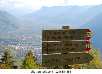 Hiking sign of the Meran High Alpine Tour (German: Meraner Hoehenweg, Ital.: Alta via di Merano). In the valley the city of Meran (South Tyrol, Italy)