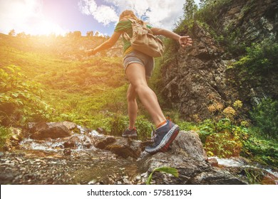 Hiking sporty girl runs along the water into the mountains. Running woman.