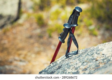 Hiking sticks standing at the stone. Travel and tourism concept.