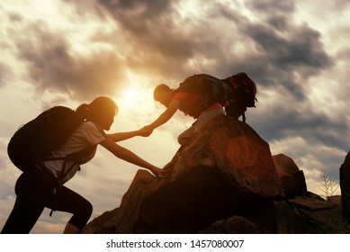 Hiking team helping each other while climbing up in a sunset. The concept of aid.