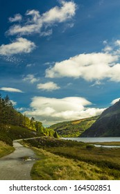 Hiking through Glendalough upper lake on a sunny day, County Wicklow, Ireland