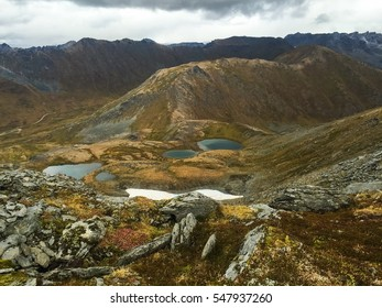 Hiking through a mountain pass with a view of small lakes in autumn.