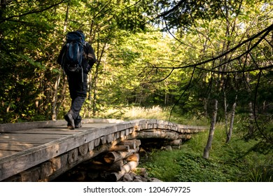 Hiking through trail with backpack on boardwalk in Mount Katahdin area in Maine