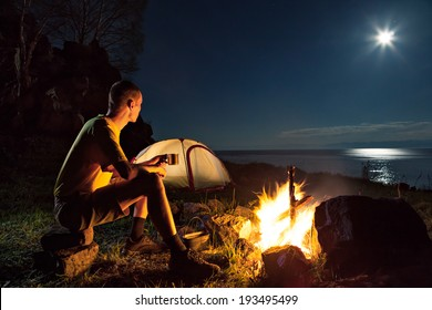 Hiking tourist have a rest in his camp at night near campfire
