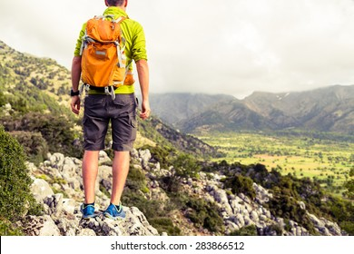77444f52f7fee9 Hiking tourist man looking at beautiful mountains inspirational landscape.  Hiker trekking with backpack on rocky