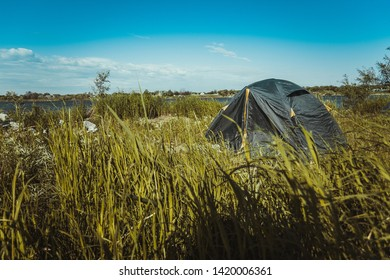Hiking tourist tent set among the grass near the riverbank. Camping activity