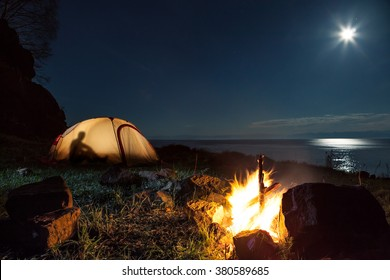 Hiking tourists have a rest in his camp at night near campfire