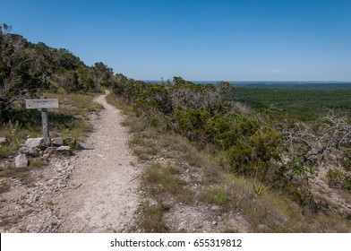 Hiking trail in Balcones National Forest, near Austin, Texas. Dirt and rock hiking trail through the low brush and trees. Hill country outdoors recreation overlooking Lake Travis.