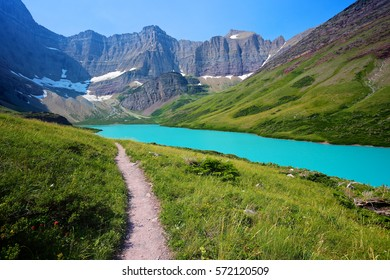 Hiking trail in beautiful alpine scenery to emerald green Cracker Lake in Glacier National Park