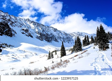 Hiking trail to climbing summit in Colorado during the late winter/early spring. Snowy mountains.