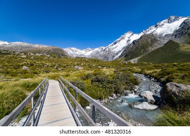 A hiking trail crosses wooden bridge over a creak high up in the mountains