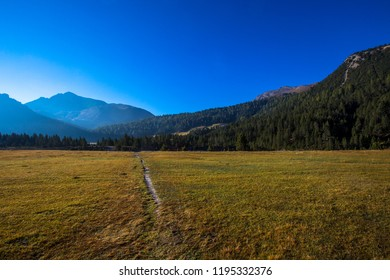 Hiking trail in the mountains near Val Mustair. Autumn landscape in the mountains of Switzerland. Countryside in the alps on a beautiful sunny day.