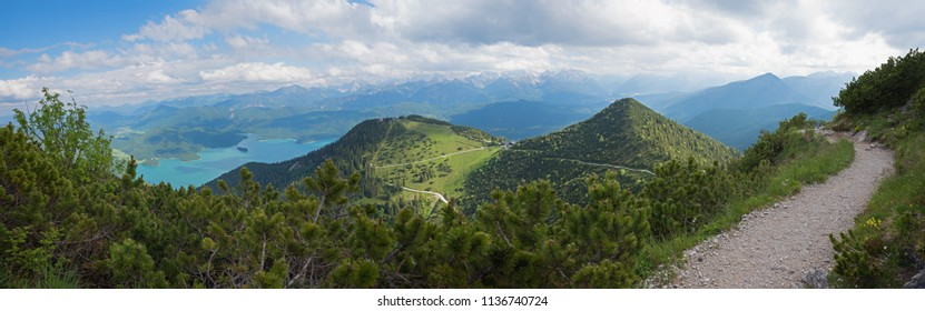 hiking trail on herzogstand mountain with view to alpine landscape bavaria and walchensee. cloudy sky.
