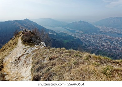 A hiking trail on the mountaintop with a beautiful panorama overlooking the lakeside town Lecco and distant mountains, from a viewpoint on Piani d'Erna by Lake Como in Lombardy, Northern Italy, Europe
