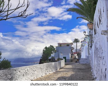Hiking trail on the north coast of Tenerife in Las Aguas. white southern caste houses and behind the dark blue atlantic. Blue sky with white clouds, southern and romantic