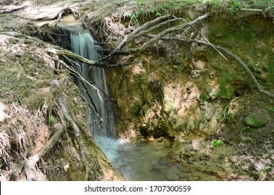 A hiking trail is severely eroded as the soil washes away creating a waterfall. Water management is needed to ensure hiking trails do not cause erosion and wear away the path causing problems.