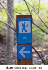 Hiking trail sign and left arrow on a post.