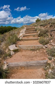 Hiking trail stairway made of wood beams and dirt, lined with rocks and sagebrush in a southwest landscape.