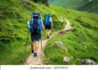 Hiking trail in Svaneti region, Georgia. Two hikers men walk on trek in mountain. Tourists with backpacks hike in highlands. Trekking in mountains. Hills and mounts in sport tourism.