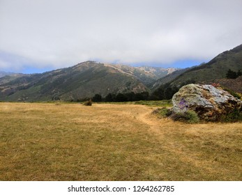 Hiking trail through an open field with foggy mountains above near Big Sur, California