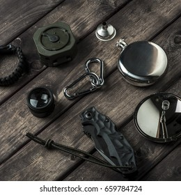 hiking travel gear on wood backdrop. Flat lay of outdoor travel equipment items for mountain camping trip.