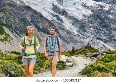 Hiking travel hikers people tramping in New Zealand mountains nature trail. Backpackers couple on Mount Cook / Aoraki Hooker valley track backpacking walking. Snow capped glacier landscape.