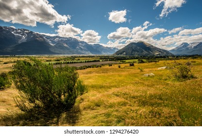 Hiking and treking in wild nature of New Zealand. Nature landscape photo of autumn meadow with green bush, hills and mountains in background. Summer travelling in Mt Aspiring national park.