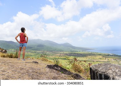 Hiking woman on travel excursion during holiday cruise looking at St Kitts and Nevis landscape. Caribbean nature during summer vacations. Young girl standing at lookout looking at viewpoint.