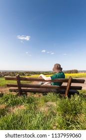 hiking woman resting on a bench on a meadow and enjoying the landscape, travel or leisure background, Odenwald, Germany, Europe